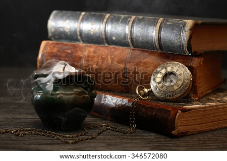 Old pocket watch on book near extinguished candle with smoke - stock photo