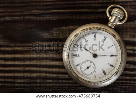 Old pocket watch on grungy wooden desk.