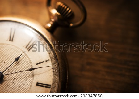 Old pocket watch on grungy wooden desk. Shot in low key and extremely shallow depth for impressional feel. Focus is on etching of clock face plate. - stock photo
