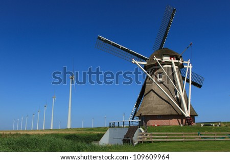 Old polder windmill 'Goliath' and modern wind turbines in a Dutch landscape. - stock photo
