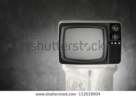 Old portable television on a plaster column. - stock photo