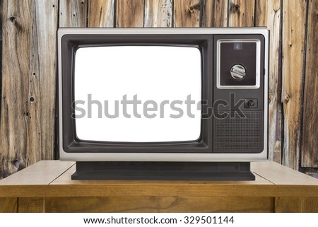 Old portable television with cut out screen and rustic wood wall. - stock photo