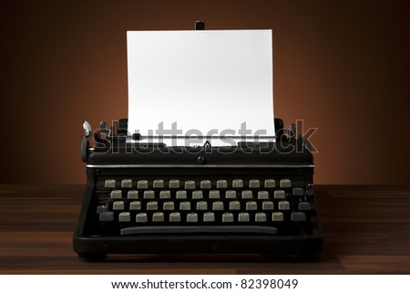 old portable typewriter with blank paper on desk - stock photo