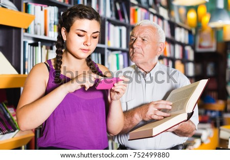 Old positive european man is choosing book while girl chatting by phone in bookstore.