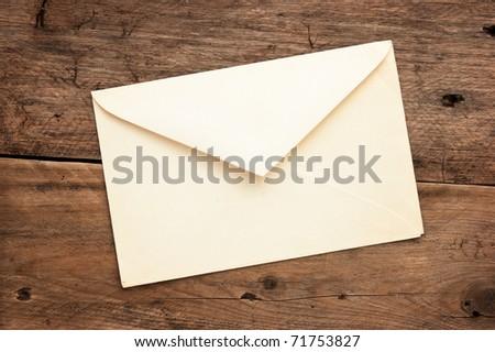 old postal envelope on wooden background - stock photo
