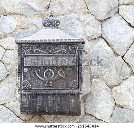 Old postbox on stone wall - stock photo