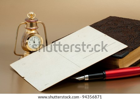 Old postcard, Ink red pen, vintage bronze clock and notepad with reflex - stock photo