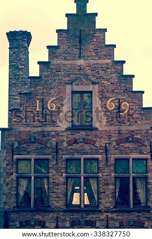Old postcard with architectural facade detail at one old building placed in Bruges, Belgium, of the 1669. Vintage processing. - stock photo