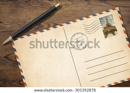 Old postcard with pen on table top view - stock photo