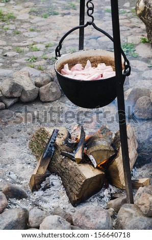 old pot for cooking over a campfire, close-up. - stock photo