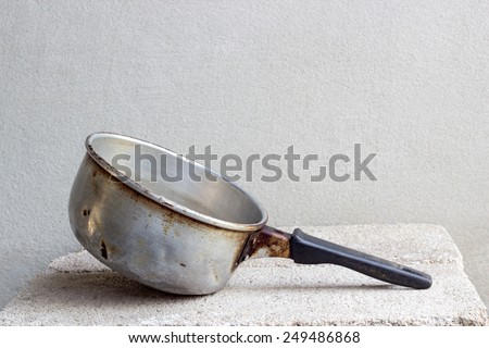 old pot with plastic handle still life on brick block and concrete wall - stock photo