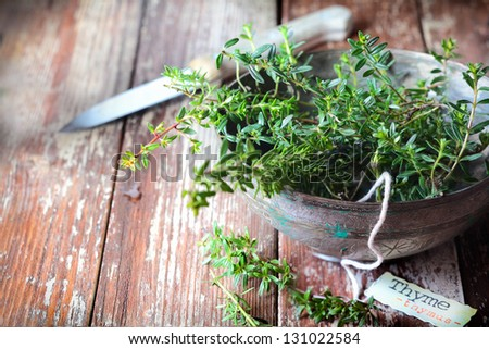 Old pottery bowl full of sprigs of fresh thyme with a decorative name label and kitchen knife on a grunge weathered wooden background - stock photo