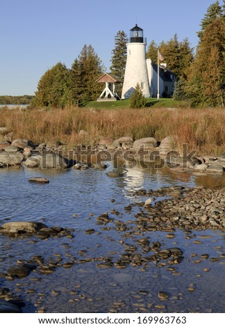 Old Presque Isle Reflection -- Old Presque isle Lighthouse reflects off the water of Lake Huron on a rocky shore. Alpena, Michigan, USA.
