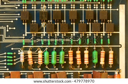 Old printed circuit board with electronic components. Closeup.