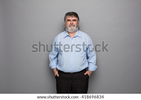 old professor with beard standing on gray background