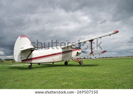Old propeller biplane taking off from the rough airstrip with stormy clouds on the background - stock photo