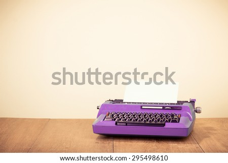 Old purple typewriter with paper blank on wooden desk. Retro instagram style filtered photo - stock photo