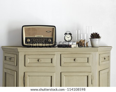 old radio and alarm-clock on the book on old sideboard - stock photo