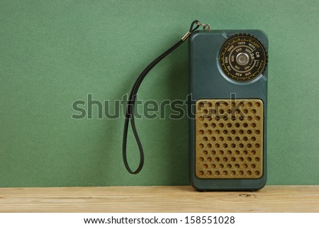 old radio on a wooden shelf in the green wall - stock photo