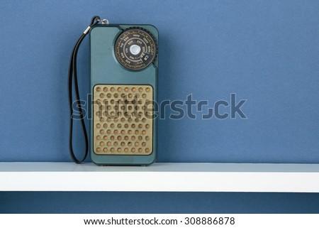 Old radio on white  shelf on blue wallpaper background - stock photo