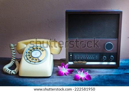 old radio, retro telephone on wooden background, vintage style. - stock photo