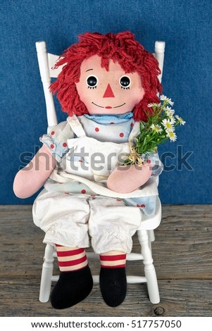 old rag doll siting on white wooden chair with daisy bouquet