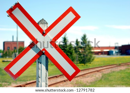 Old railroad crossing stop sign in a rural scene with shallow focus