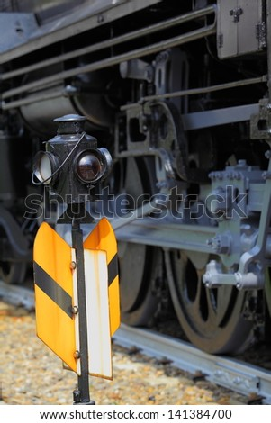 Old railroad signal in front of steam locomotive wheels/Railroad Signal and Steam Locomotive - stock photo