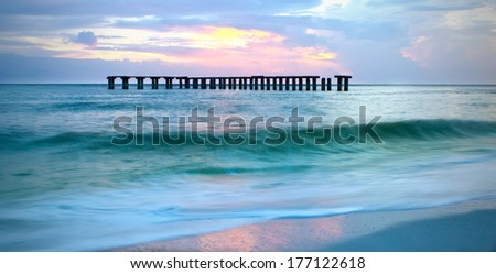 old railroad struts in the sea at Boca Grande, Florida at sunset - stock photo