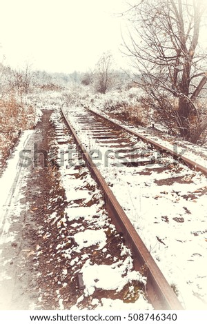 Old railway bridge in the snow. Industrial area. Wide angle. Old toned photo.