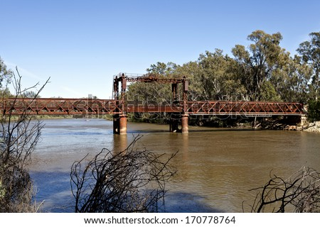 Old railway bridge over the Murray River in Tocumwal on the border between Victoria and New South Wales, Australia. It has three spans including the central lift span. - stock photo