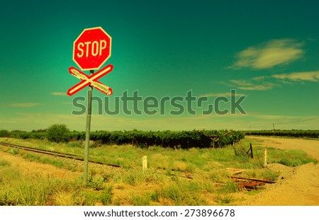 Old railway crossing sign in arid landscape  - stock photo
