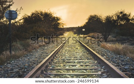 Old railway through the African semi desert landscape, sunset, retro style - stock photo