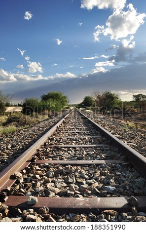 Old railway tracks in interesting light of setting sun - stock photo