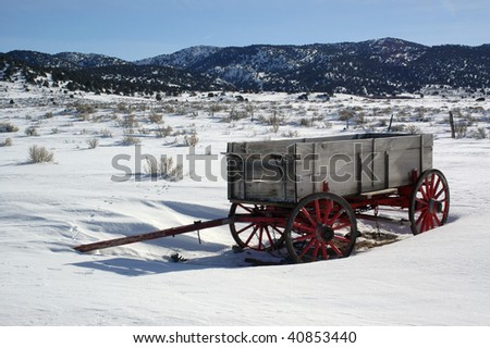 Old ranch wagon with red wheels in snowy field - stock photo