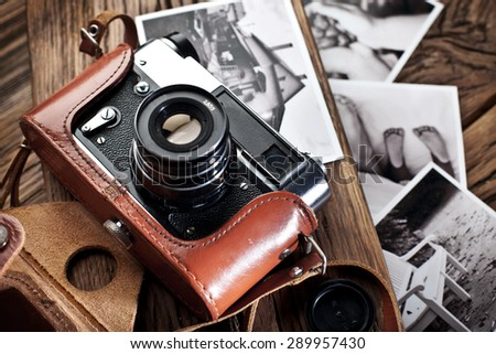 Old rangefinder camera and black-and-white photos on the old wooden table. - stock photo