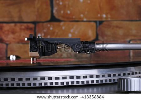 old record player stylus, brick wall - stock photo