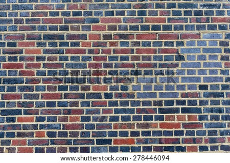 Old red and blue brick wall in a background image - stock photo