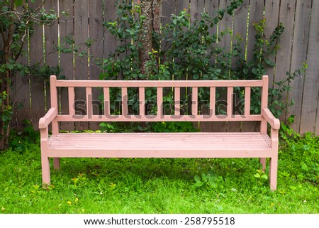 Old red bench stands on green grass near wooden fence in park - stock photo