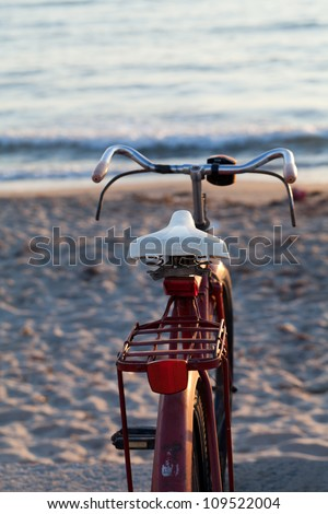 Old red bike on the beach - stock photo