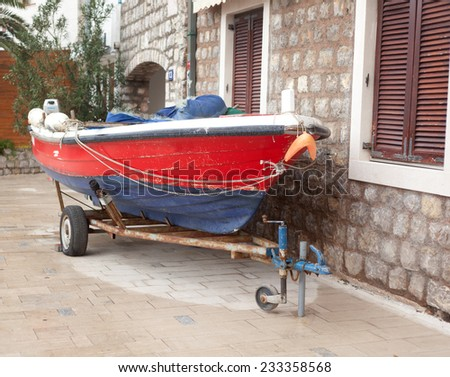 Old red boat parked near the house - stock photo