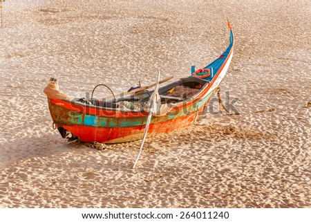 Old red boat stranded on the beach of Costa Nova, Portugal. - stock photo