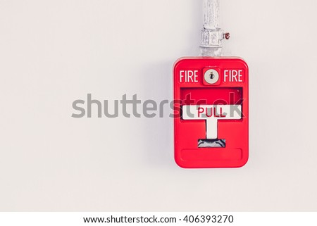 Old red box fire alarm  on cement wall - stock photo
