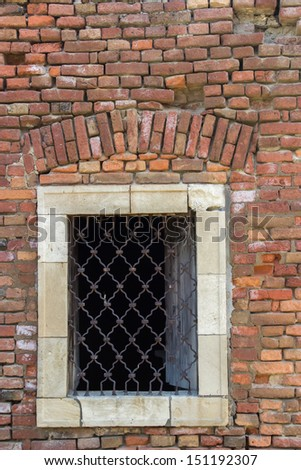 Old red brick wall  with bars window at the fort