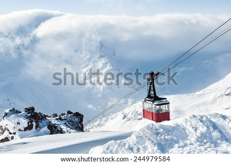 Old red cable car at mountain. Ski resort Elbrus. Caucasus, Russian Federation. Beautiful winter landscape with snow covered mountains. - stock photo