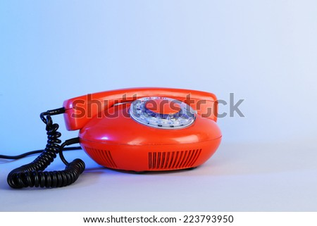 Old red disk phone on blue background - stock photo