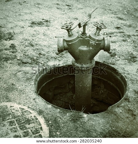 old red fire hydrant in manhole cover, black and white photo - stock photo