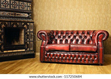Old Red Genuine Leather Sofa Near The Fireplace - stock photo