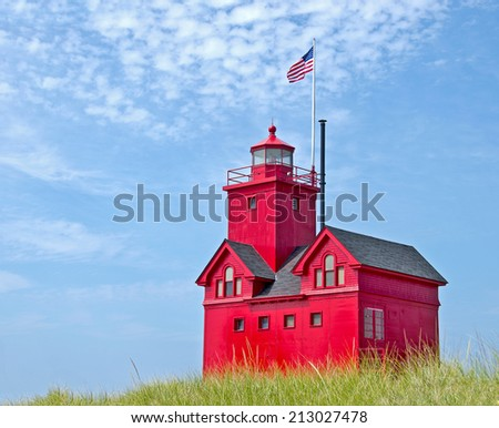 old red lighthouse in dune grass in Holland, Michigan - stock photo