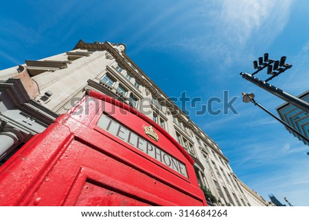 Old Red Phone Booth with London buildings on background. - stock photo